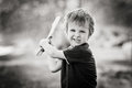 Angry little boy holding sword glaring with a mad face at the camera outdoors in park monochrome conversion Royalty Free Stock Photos