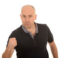 Angry man with clenched fist middle aged bald white background Stock Photos