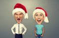Angry man and happy woman christmas photo of men women over grey background Royalty Free Stock Photo