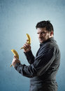 Angry man holding bananas like pistols looking camera rage face expression Royalty Free Stock Image