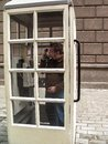 Angry man standing in a white telephone booth and screaming into the phone