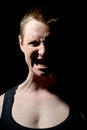 Angry man white in a black t shirt shouts in anger on black background Royalty Free Stock Image