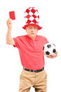 Angry mature football fan with ball giving a red card isolated on white background Stock Photos