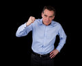 Angry middle age business man shaking fist black background Stock Photos