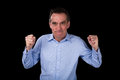 Angry middle age business man shaking fists frustration black background Royalty Free Stock Image