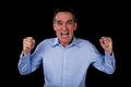 Angry shouting middle age business man shaking fists black background Stock Image