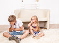 Angry siblings sitting on the carpet Stock Photo