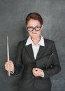 Angry teacher with pointer on the school blackboard background Royalty Free Stock Photos