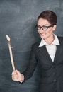 Angry teacher with wooden stick on the school blackboard background Royalty Free Stock Photo