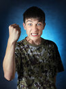 Angry teenager in camouflage t shirt threaten with his fist on the dark background Stock Photography