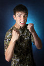 Angry teenager in camouflage t shirt threaten with his fists on the dark background Royalty Free Stock Photography