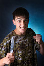 Angry teenager with knife on the dark background Royalty Free Stock Photo