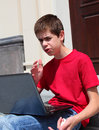 Angry teenager with a laptop computer screaming at his Royalty Free Stock Photography