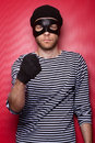Angry thief classic standing at the red background Royalty Free Stock Image
