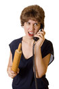 An angry wife woman with a rolling pin on the phone screaming isolated on white background Royalty Free Stock Photos