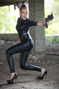 Angry woman with gun in ruins screaming fetish leather catsuit holding a handgun old fabric Stock Photos