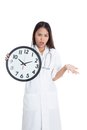 Angry young asian female doctor with a clock isolated on white background Stock Photos
