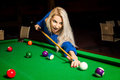 Angry young blonde girl plays billiard at pool table Royalty Free Stock Photo