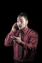 Angry young businessman talking on phone isolated a black background Royalty Free Stock Photography