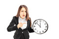 Angry young businesswoman pointing on a wall clock isolated white background Royalty Free Stock Photos