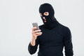 Angry young man in balaclava using cell phone Royalty Free Stock Photo