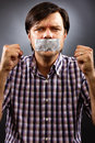 Angry young man with duct tape over his mouth against gray background conceptual image Royalty Free Stock Photos