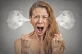 Angry young woman steam coming out of ears screaming closeup portrait blowing having nervous atomic breakdown isolated grey wall Royalty Free Stock Photos