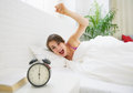 Angry young woman wants to break awakened her alarm clock in living room Stock Photo