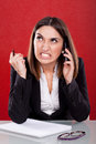 Angry young woman at work talking on the phone Royalty Free Stock Photos
