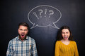 Angry youple shouting over blackboard background young couple standing and Royalty Free Stock Image