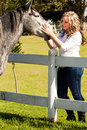 Animal affection a cute caucasian girl with curly blond hair leaning over the white picket fence stroking a healthy gray horse on Stock Photo