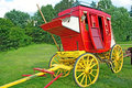 Anitque stage coach antique red and yellow in the field Stock Photography
