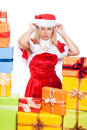 Annoyed christmas woman in santa costume surrounded by presents isolated on white background Stock Photos