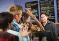 Annoyed male cafe worker with long line Royalty Free Stock Photography