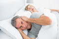Annoyed man blocking his ears from noise of wife snoring men at home in bedroom Stock Photography