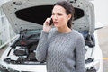 Annoyed woman on the phone beside her broken down car in a park Royalty Free Stock Photo