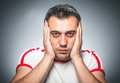 Annoying or worried young man over dark gray background Royalty Free Stock Image