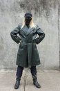 Anonymous blonde woman standing masked in a leather coat and sunglasses Royalty Free Stock Photography