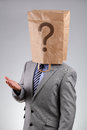 Anonymous businessman with paper bag on his head wearing a a question mark concept for business recruitment mystery shopper Royalty Free Stock Images