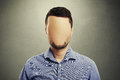 Anonymous man with blank face against dark background Royalty Free Stock Image