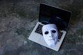 Anonymous mask to hide identity on computer laptop - internet criminal and cyber security threat concept Royalty Free Stock Photo