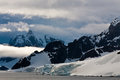Antarctic coast with snow rocks and clouds and icebergs Stock Image