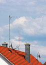 Antennas and chimneys on the roof top of red Stock Photography