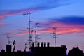 Antennas at sunset on the roofs in milan italy Stock Photography