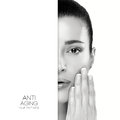 Anti aging and skincare concept with a monochrome half face portrait of a serene young woman with her manicured nails raised to Stock Images
