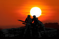 Anti Aircraft fire machine gun and three soldier in silhouette