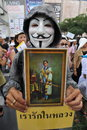Anti government white mask protest in bangkok an protester wearing a guy fawkes and holding a portrait of the current thai king Royalty Free Stock Photography