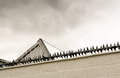 Anti intruder spikes on top of a white brick wall to deter burglars and thieves from climbing a boundary Stock Image