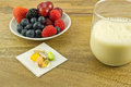 Anti oxidants on table berries oxidant supplements and a cup of soy milk wooden Stock Images