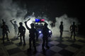 Anti-riot police give signal to be ready. Government power concept. Police on chessboard. Smoke on a dark background with lights.